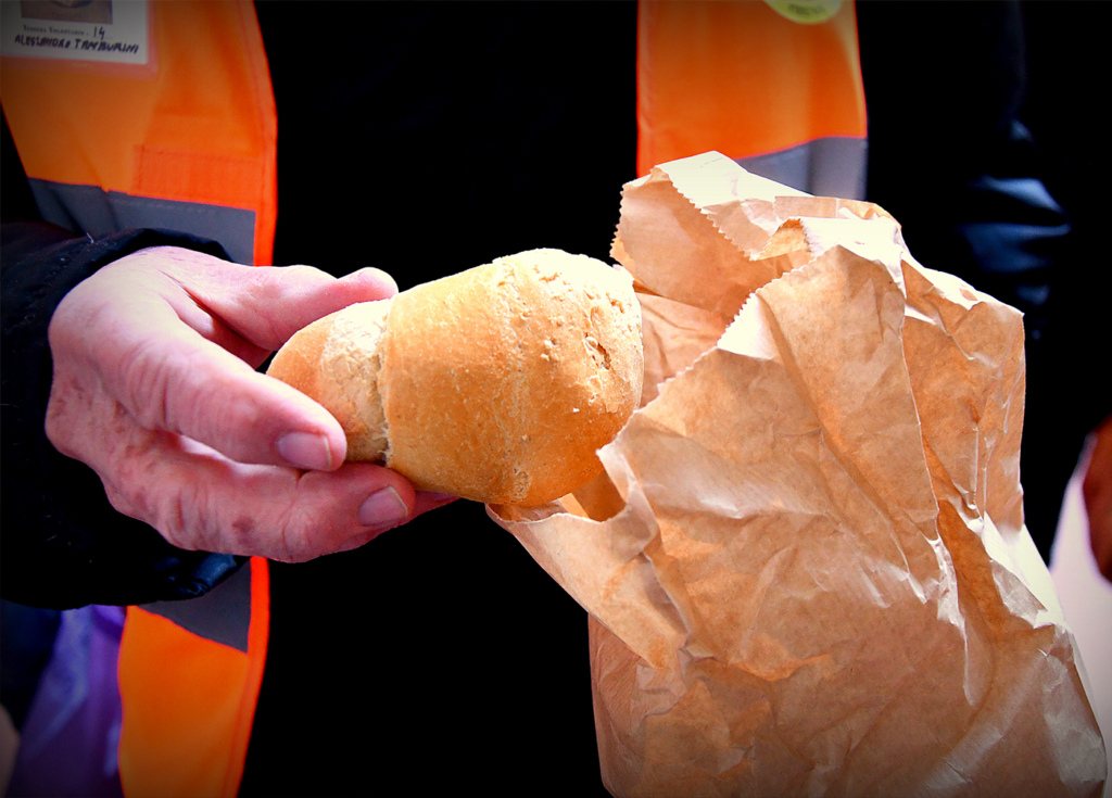Immagine di un volontario di Pane Quotidiano che offre una pagnotta prendendola da un sacchettino di carta